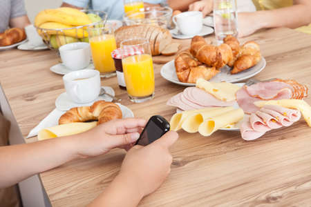mealtime: Close-up on teenager texting on her mobile phone in the kitchen while the rest of the family enjoy breakfast Stock Photo