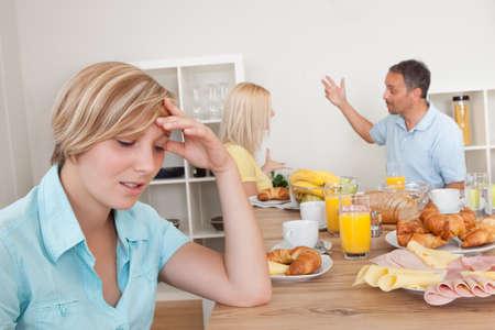strife: Un giovane figlia adolescente sembra molto scoraggiato e depresso ai suoi genitori che stanno discutendo in background Archivio Fotografico