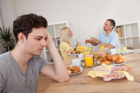 A young teenage son looks very downhearted and despondent at her parents who are arguing in the background photo