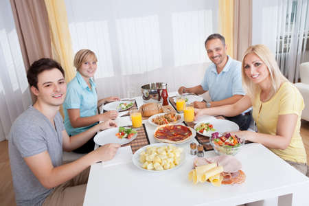 Young happy family with teenage children sitting down to eat a cold lunch of meat and salads photo