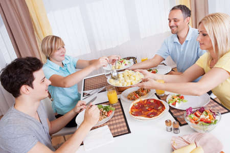 Happy family with a teenage son and daughter seated at the table serving themselves to a healthy cold dinner with meat and salads photo