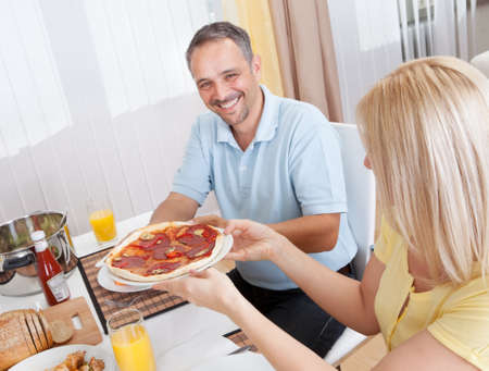 Cheerful middle-aged couple eating lunch at home photo