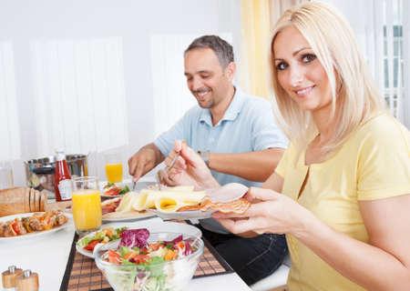 pareja comiendo: Alegre pareja de mediana edad almuerzo comer en casa