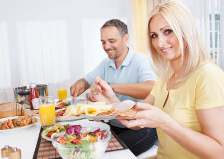 sustenance: Cheerful middle-aged couple eating lunch at home Stock Photo