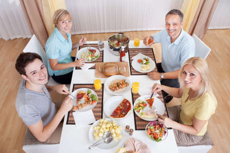 topdown: Young happy family with teenage children sitting down to eat a cold lunch of meat and salads