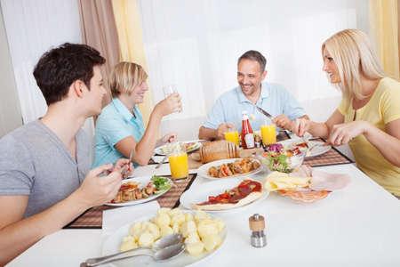 familia cenando: Atractivo familia disfrutando de una comida saludable juntos sentados alrededor de la mesa