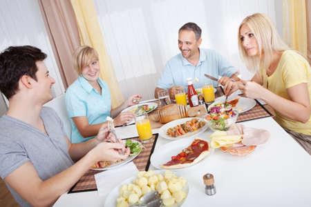 dialogo: Atractivo familia disfrutando de una comida saludable juntos sentados alrededor de la mesa