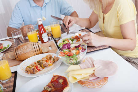 Attractive family enjoying a healthy meal together seated around the table photo