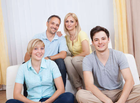 Smiling attractive young family with a teenage son and daughter posing together in group portrait Stock Photo - 15496780