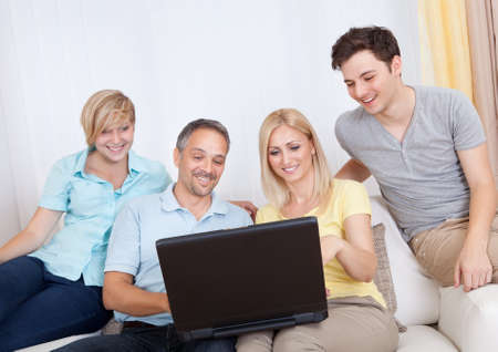 Smiling family together sitting on the couch with laptop photo