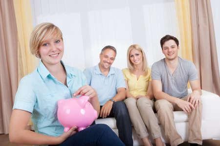 apoyo familiar: Atractiva chica adolescente joven que pone una moneda en una alcancía rosa