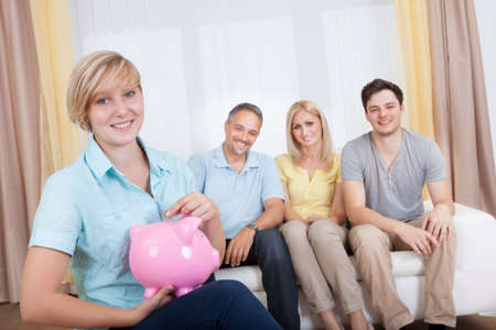 nestegg: Attractive young teenage girl putting a coin in a pink piggy