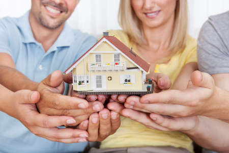 buy house: Happy parents with their teenage son and daughter holding a model house conceptual of setting a goal for home ownership