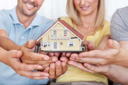 planificacion familiar: Padres felices con su hijo e hija adolescente que sostiene una casa modelo conceptual de fijar una meta para la propiedad de la vivienda