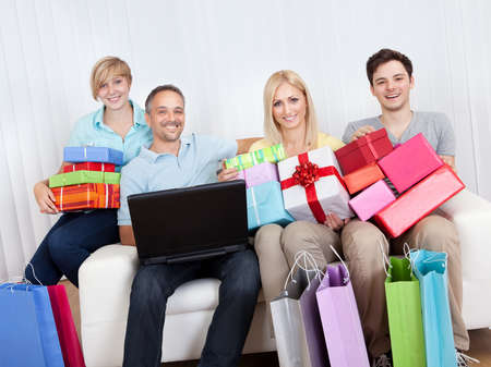 Happy family of online shoppers laden with gifts sitting around the father who is sitting with his laptop computer on his lap photo