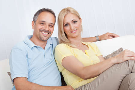 contented: Smiling loving attractive middle-aged couple sitting close together relaxing on a sofa