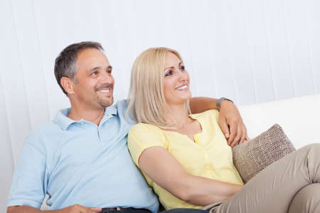 Smiling loving attractive middle-aged couple sitting close together relaxing on a sofa photo
