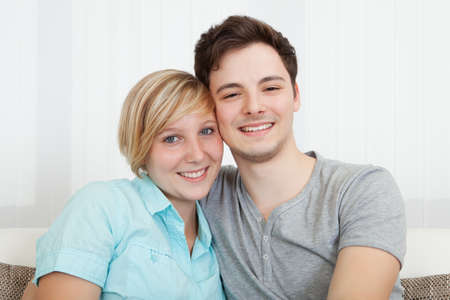 contented: Smiling loving attractive young couple sitting close together relaxing on a sofa