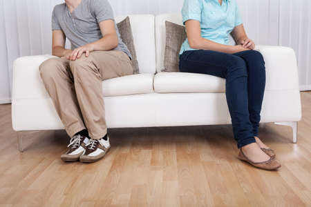 withdrawn: Brother and sister have had an argument and are sitting at opposite ends of a sofa