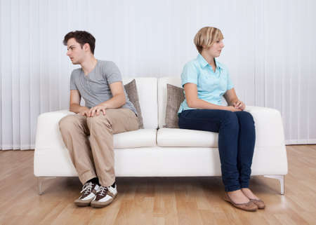 ends: Brother and sister have had an argument and are sitting at opposite ends of a sofa