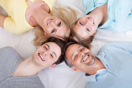 Joyful family lying in a circle on their backs looking up at the camera with their heads close together photo