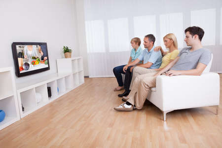 Family with teenage children sitting together on a sofa in the living room watching widescreen television photo