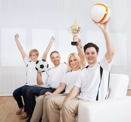 jubilation: Ecstatic family sitting together on a couch celebrating a win with their arms raised in jubilation holding aloft a ball and trophy Stock Photo