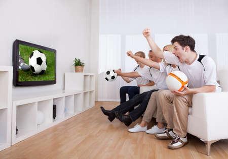 personas viendo television: Jubilant familia viendo la televisión, ya que alentar a su equipo local en una competición deportiva Foto de archivo