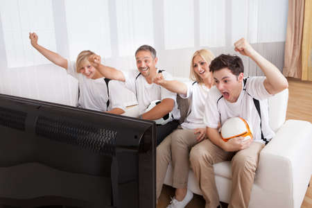 Jubilant family watching television as they cheer on their home side in a sporting competition Stock Photo