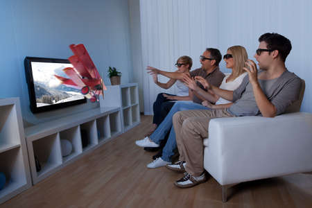 stereo: Conceptual image of a family watching 3D television and stretching out their hands as though to touch the image on the screen