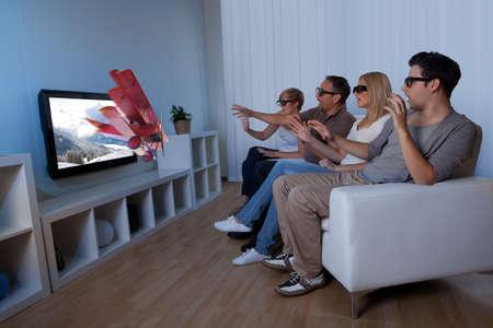 viewing: Immagine concettuale di una famiglia guardare la televisione 3D e allungando le mani come per toccare l'immagine sullo schermo