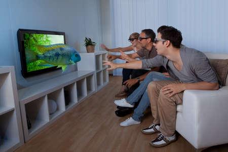 personas viendo television: Imagen conceptual de una familia viendo la televisión en 3D y extendiendo las manos como si quisiera tocar la imagen en la pantalla