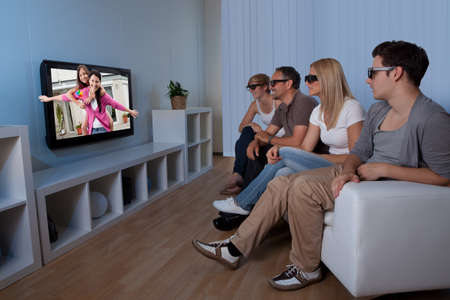 Family with teenage children sitting together on a couch eating bowls of popcorn wearing 3d glasses and watching the television photo