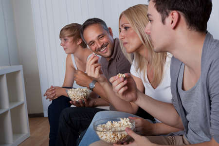 bowls of popcorn: Family with teenage children sitting together on a couch eating popcorn and watching the television Stock Photo