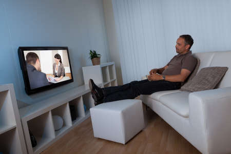 flatscreen: Man recline comfortably on his living room couch watching home movies on his widescreen television set Stock Photo