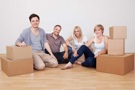 Happy family moving into the new home sitting in an empty room on the floor with small stack of cardboard boxes photo