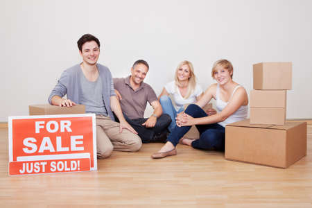 sold small: Happy family packing up their home sitting in an empty room on the floor with a sold sign and a small stack of cardboard cartons