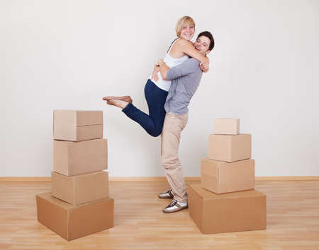 Happy young couple in a close ecstatic embrace smiling happily as they stand surrounded by cartons in their new home photo