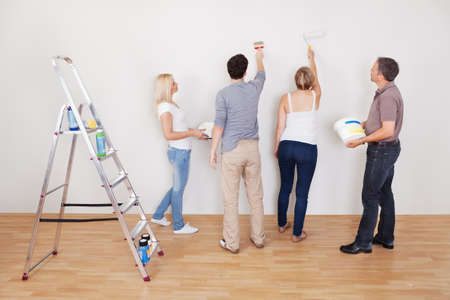Family teamwork during home maintenance as the children repair the surface of the wall for their parents to paint Stock Photo - 15225899