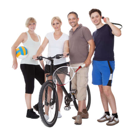 Portrait of a sporting family each holding their equipment of choice with a volley ball photo