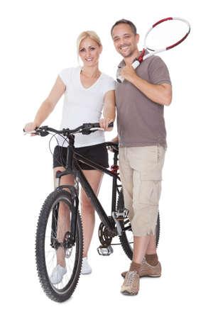 edad media: Montar sanos de mediana edad los padres que disfrutan de un estilo de vida activo en pie al aire libre con una raqueta de tenis y bicicletas