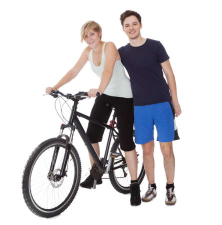 Fit healthy young couple who enjoy an active outdoor lifestyle standing with  bicycle photo