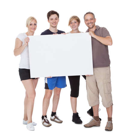 Happy family with two teenage children holding up a blank placard or sign with copyspace for your advertising of announcement photo