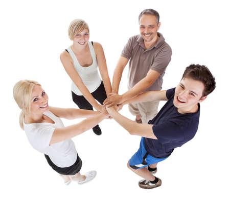 manos unidas: Vista de ángulo alto de una familia feliz con un hijo adolescente y una hija de la mano Foto de archivo