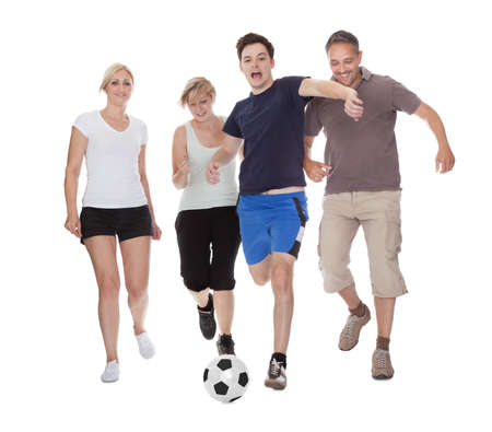 women playing soccer: Active family with fit parents and two teenagers playing soccer running after a ball isolated on white Stock Photo
