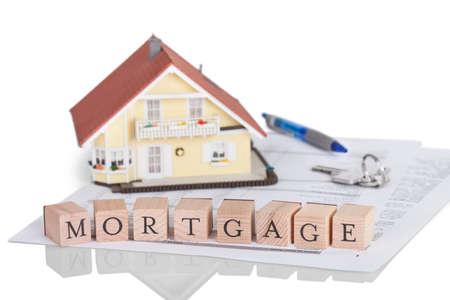 equidad: Bloques de madera que deletrean la palabra hipoteca en un documento legal