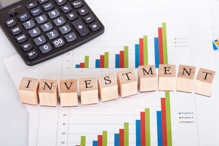 volatility: Bloques de madera que llevan la Inversi�n letras en una p�gina de gr�ficos que representan las estad�sticas financieras con una calculadora al lado Foto de archivo