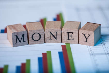 statics: Wooden blocks with the lettering Money on top of ascending bar graphs analyzing the statics and performance of shares within the market
