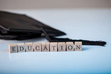 Education concept with the alphabet letters for Education spelt out on wooden blocks beside a graduation cap photo