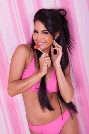 paletas de caramelo: Sexy mujer sensual con un cuerpo curvil�neo de pie chupando una piruleta en un bikini rosado sobre un fondo rosa con rayas